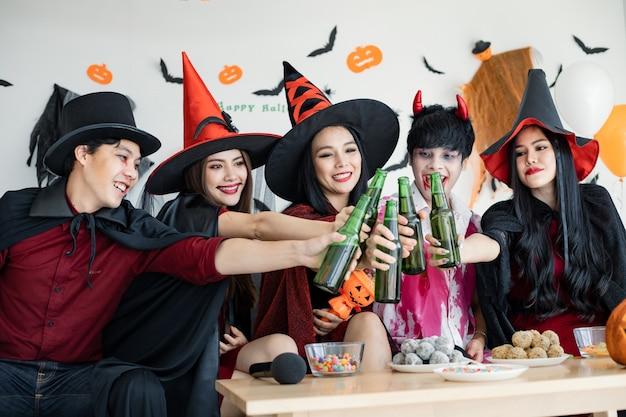 Gangue de jovens asiáticos fantasiados de bruxa, feiticeiro e celebram a festa de halloween para uma garrafa de tilintar e uma bebida no quarto. o grupo adolescente tailandês com comemora o halloween. festa de halloween do conceito em casa.