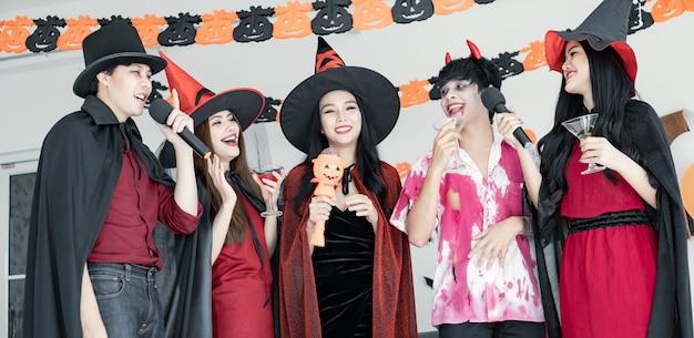 Gangue de jovens asiáticos fantasiados de bruxa, feiticeiro e festa de halloween para cantar uma música e beber, sobremesa na sala. grupo adolescente tailandês com celebrar o halloween. festa de halloween do conceito em casa.