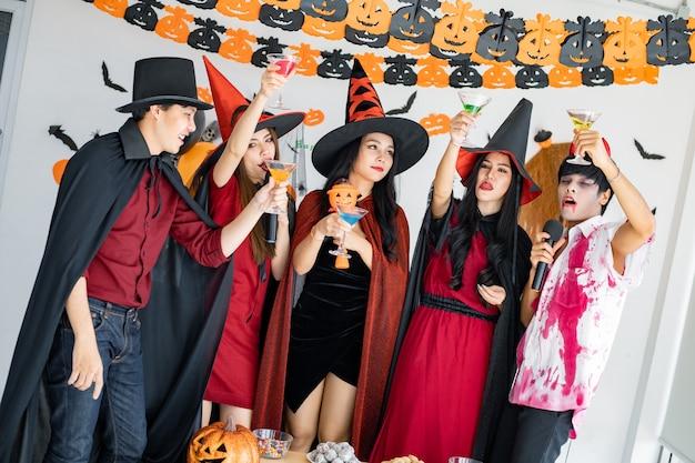 Gangue de jovens asiáticos fantasiados de bruxa, feiticeiro e festa de halloween para cantar uma música e beber, sobremesa na sala. o grupo adolescente tailandês com comemora o halloween. festa de halloween do conceito em casa.