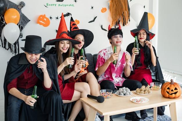 Gangue de jovens asiáticos fantasiados de bruxa, feiticeiro e festa de halloween para dançar e beber e bêbados no quarto. o grupo adolescente tailandês com comemora o halloween. festa de halloween do conceito em casa.