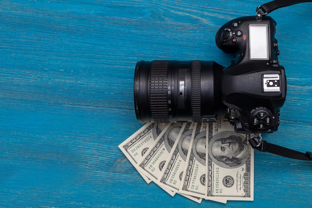 Ganhe dinheiro na câmera dslr da internet, dólares, laptop, sobre fundo azul de madeira, vista superior