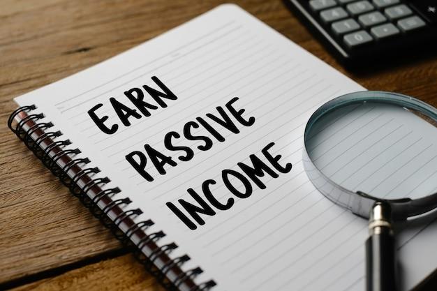 Ganhe renda passiva, tipografia de palavras de texto escrita em livro contra fundo de madeira, conceito inspirador motivacional de vida e negócios