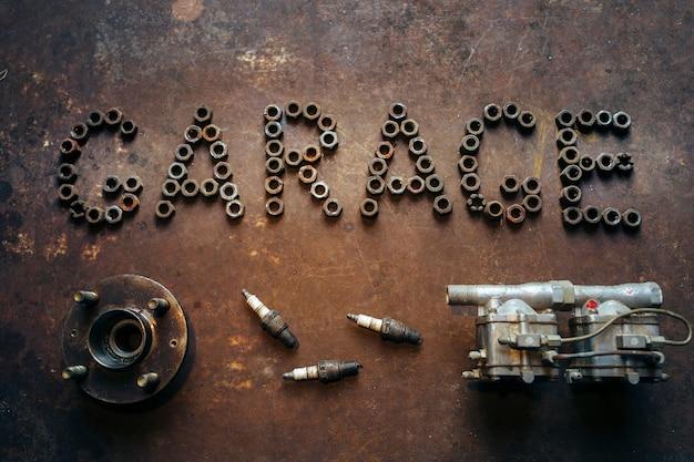 Garagem de palavras de nozes e peças sobressalentes na mesa de metal