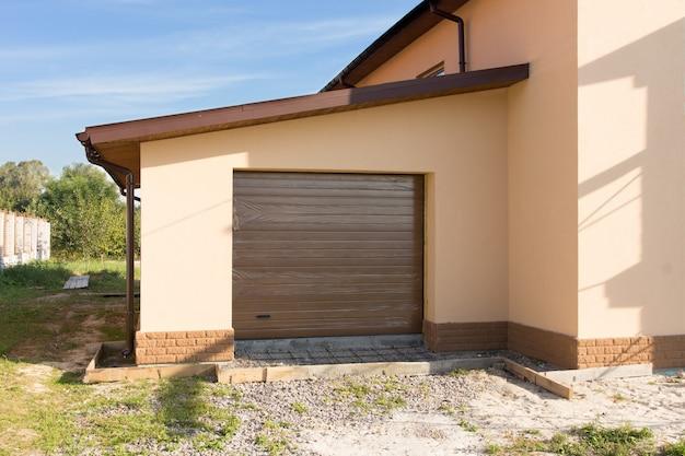 Garagem única recém-construída com uma porta de enrolar fechada anexada à borda de uma nova construção de casa