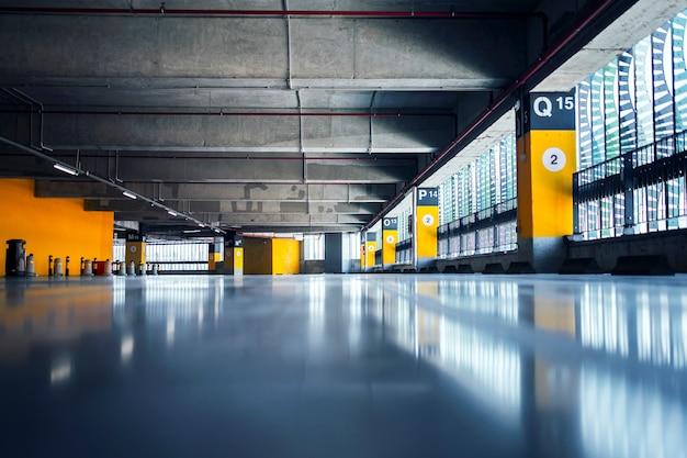 Garagem vazia com estacionamentos com teto e piso de concreto e pilares marcados com números
