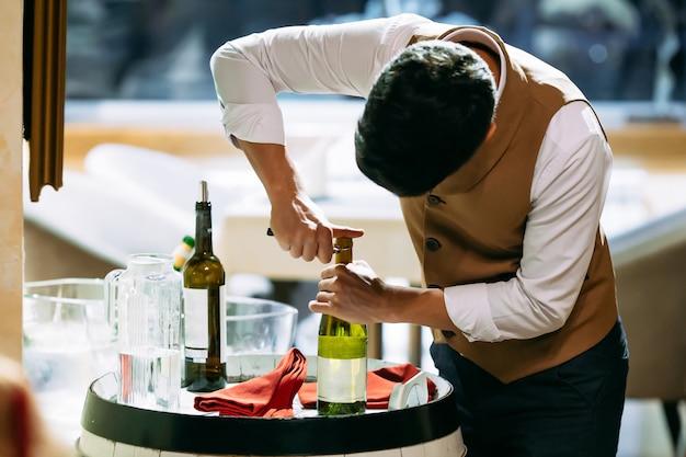 Garçom, abrindo a garrafa de vinho branco no restaurante