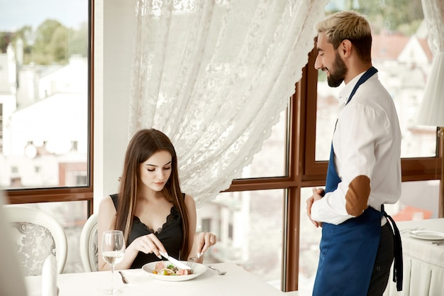 Garçom, aguardando um feedback sobre um prato servido de um revisor no restaurante