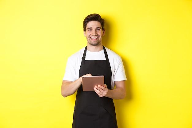 Garçom bonitão anotando os pedidos, segurando um tablet digital e sorrindo, usando avental preto uniforme, de pé sobre a parede amarela