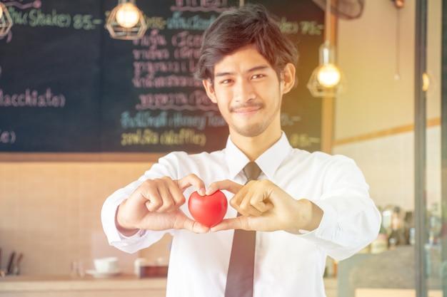 Garçom bonitão está servindo e segurando coração com amor no dia dos namorados
