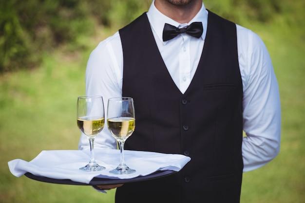 Garçom bonitão segurando uma bandeja com dois copos de vinho