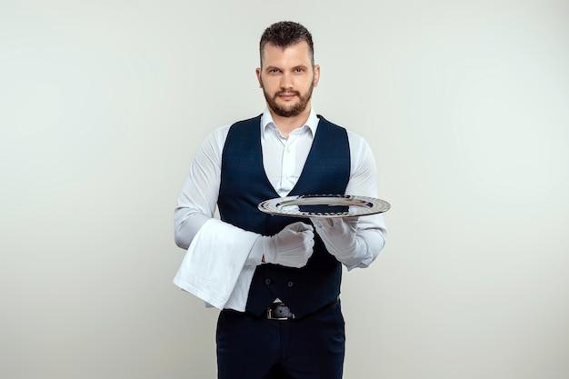 Garçom bonito, de camisa branca, segurando uma bandeja de prata. o conceito de servir o pessoal que atende os clientes em um restaurante.