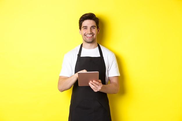 Garçom bonito recebendo pedidos, segurando o tablet digital e sorrindo, vestindo uniforme de avental preto, em pé sobre um fundo amarelo.