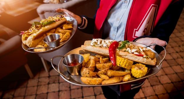 Garçom, carregando dois pratos com grandes cachorros-quentes e batatas fritas. restaurante.