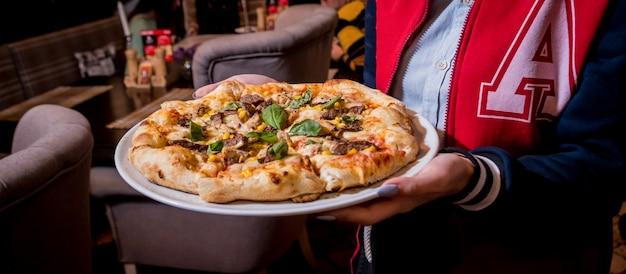 Garçom, carregando prato com saborosa pizza com frango e legumes. restaurante.