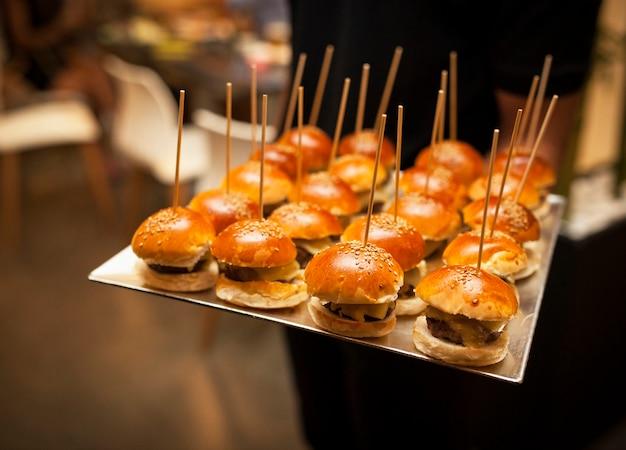 Garçom carregando uma bandeja cheia de mini cheeseburgers de alta qualidade em um bom restaurante.