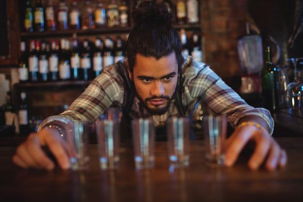 Garçom colocando copos de bebida no balcão