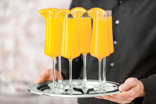 Garçom com copos de saboroso coquetel de mimosa em banquete