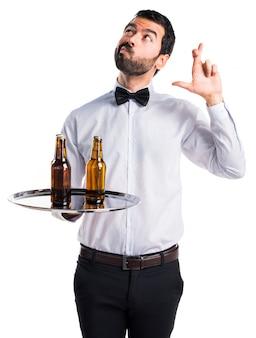 Garçom com garrafas de cerveja na bandeja com os dedos cruzados
