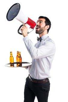 Garçom com garrafas de cerveja na bandeja gritando por megafone