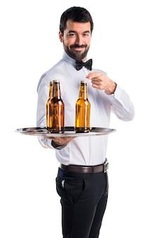 Garçom com garrafas de cerveja na bandeja