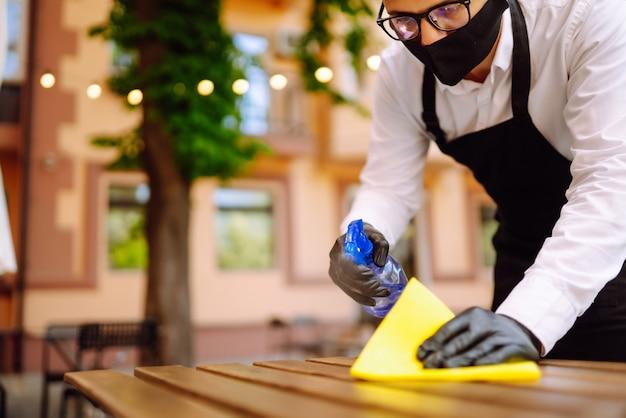 Garçom com máscara protetora e luvas desinfetando a mesa do restaurante para o próximo cliente.