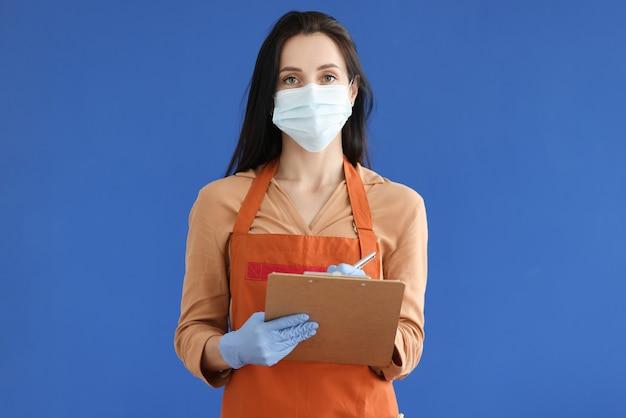 Garçom com máscara protetora e luvas escrevendo o pedido no fundo azul