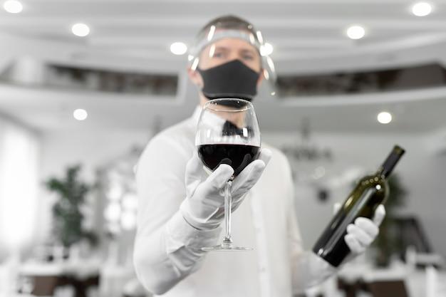 Garçom com uma máscara protetora com uma taça de vinho tinto nas mãos.