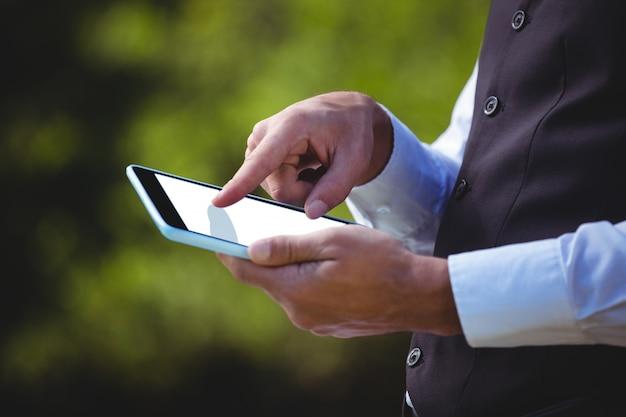 Garçom considerável usando computador tablet