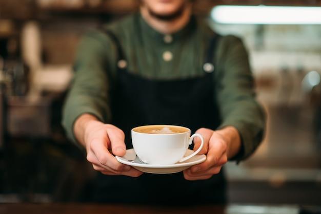 Garçom de avental preto estende uma xícara de café com creme nas mãos.