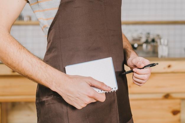 Garçom de colheita com caderno e caneta