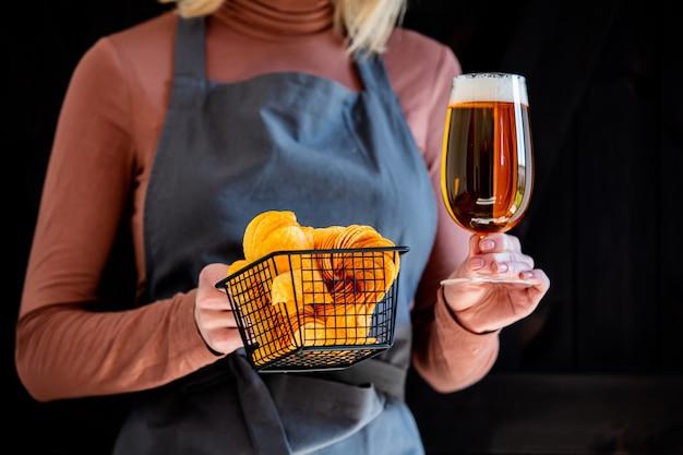 Garçom de mulher detém cerveja e batatas fritas