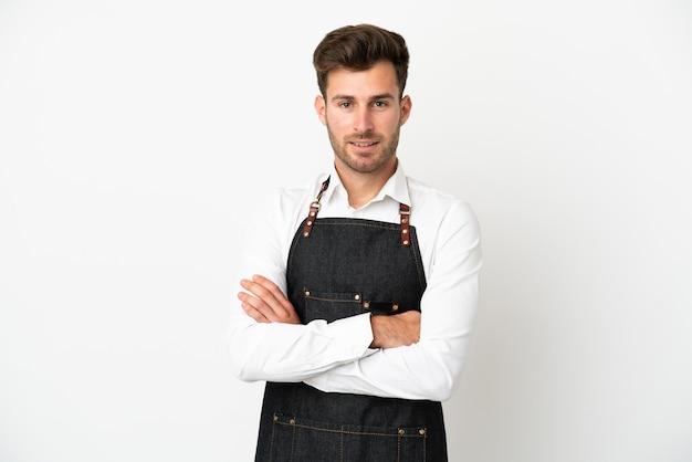 Garçom de restaurante caucasiano isolado no fundo branco mantendo os braços cruzados na posição frontal