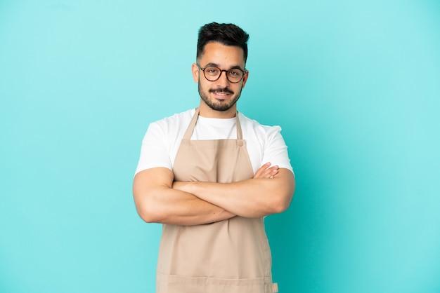 Garçom de restaurante homem caucasiano isolado em fundo azul mantendo os braços cruzados na posição frontal