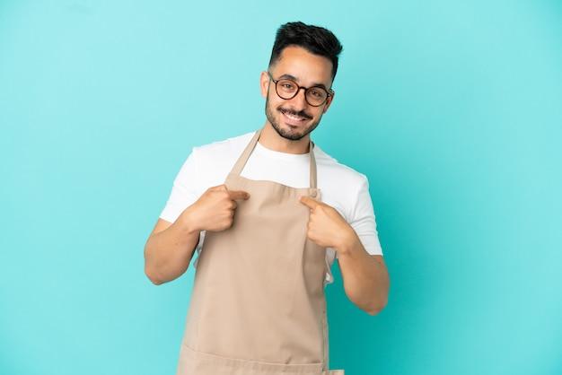 Garçom de restaurante, homem caucasiano, isolado em um fundo azul com expressão facial surpresa
