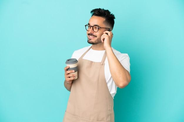 Garçom de restaurante, homem caucasiano, isolado em um fundo azul, segurando um café para levar e um celular
