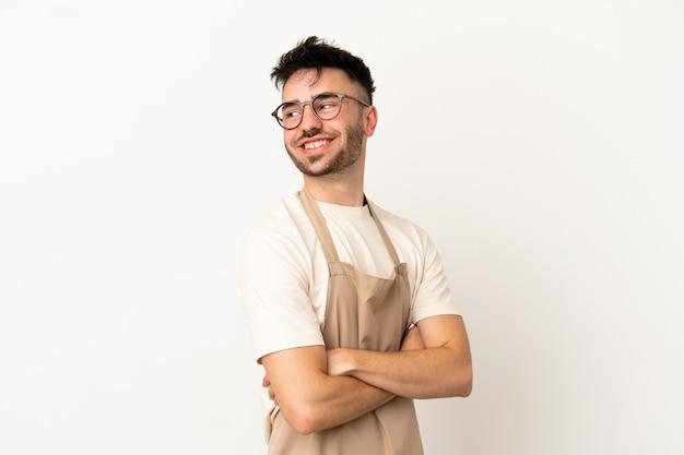 Garçom de restaurante homem caucasiano isolado no fundo branco com os braços cruzados e feliz
