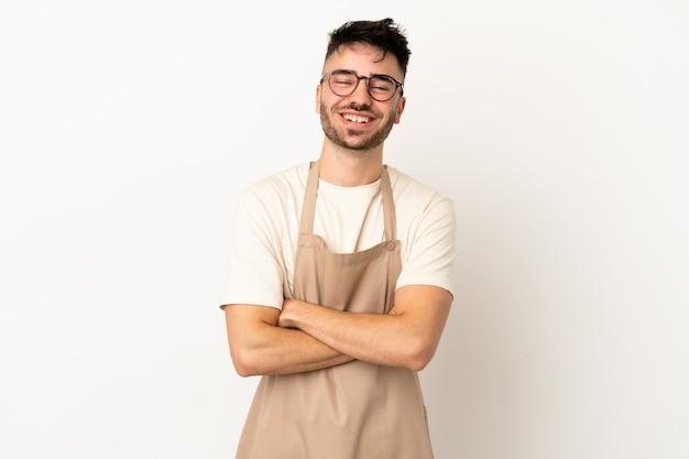 Garçom de restaurante homem caucasiano isolado no fundo branco mantendo os braços cruzados na posição frontal