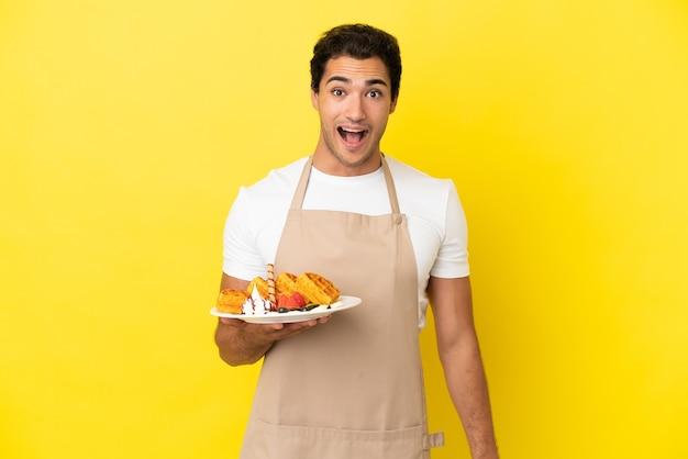 Garçom de restaurante segurando waffles sobre fundo amarelo isolado com expressão facial surpresa
