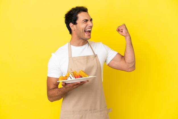 Garçom de restaurante segurando waffles sobre fundo amarelo isolado comemorando vitória
