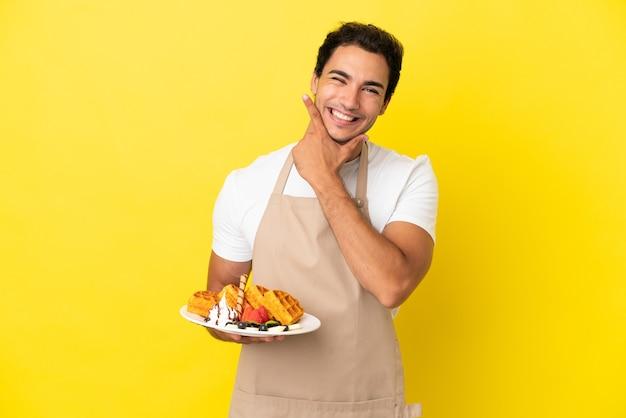 Garçom de restaurante segurando waffles sobre fundo amarelo isolado feliz e sorridente