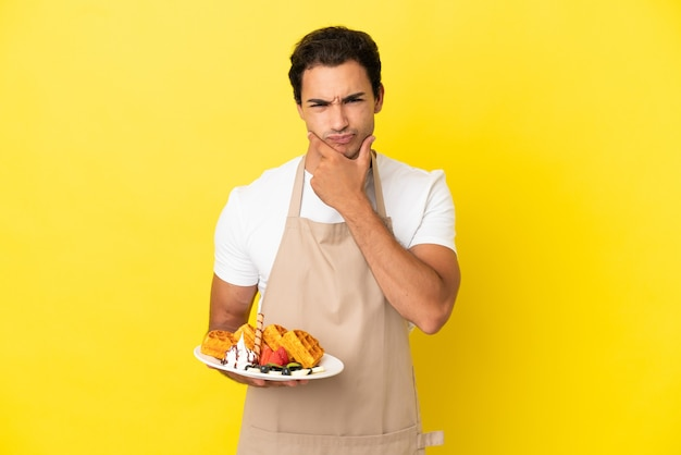 Garçom de restaurante segurando waffles sobre fundo amarelo isolado pensando