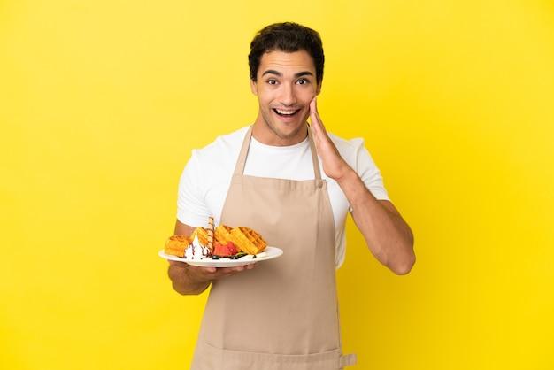Garçom de restaurante segurando waffles sobre um fundo amarelo isolado com expressão facial surpresa e chocada