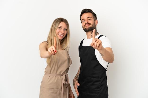 Garçom de restaurante sobre fundo branco isolado mostrando e levantando um dedo