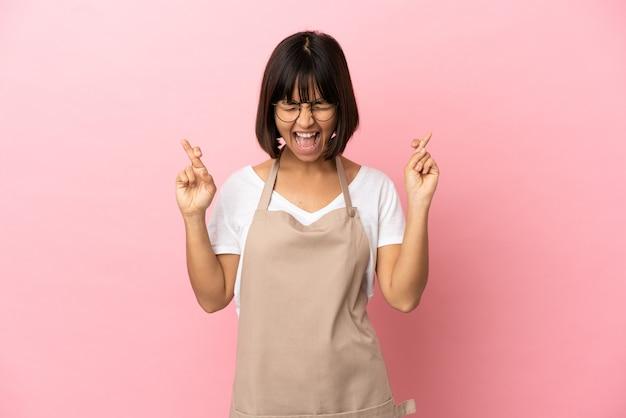 Garçom de restaurante sobre fundo rosa isolado cruzando os dedos