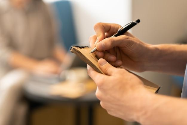 Garçom de um café ou restaurante moderno segurando uma caneta sobre a página do bloco de notas enquanto faz anotações sobre o pedido do cliente