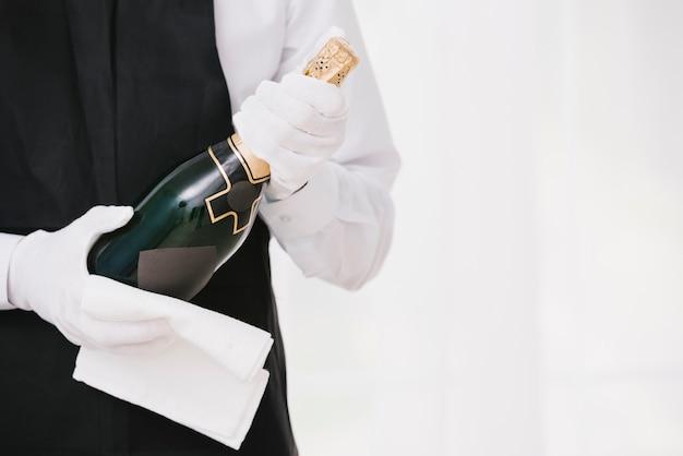 Garçom de uniforme, apresentando champanhe