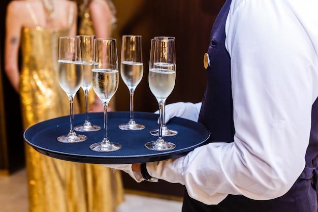Garçom de uniforme com taças de champanhe em uma bandeja