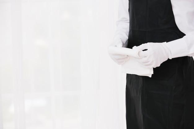 Garçom de uniforme segurando o pano