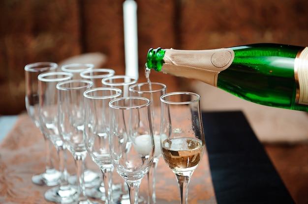 Garçom derrama champanhe em copos, evento de luxo.