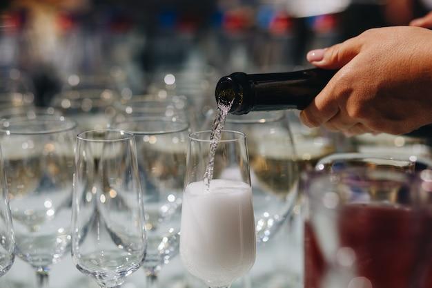 Garçom, derramando champanhe em copos em uma restauração
